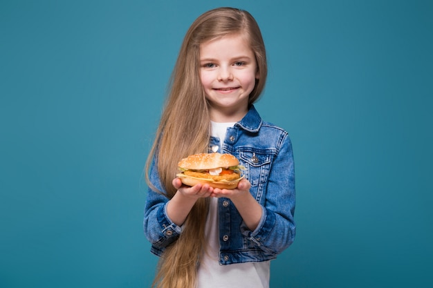 Menina bonita na jaqueta jeans com cabelos castanhos compridos segurar um hambúrguer