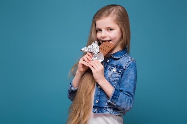 Menina bonita na jaqueta jeans com longos cabelos castanhos segurar barra de chocolate
