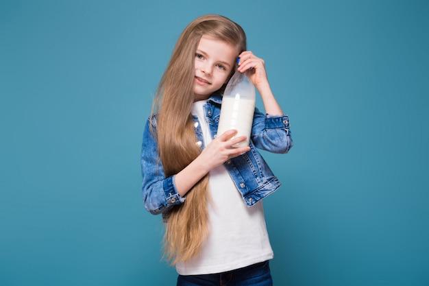 Menina bonita na jaqueta jeans com longos cabelos castanhos segurar o recipiente com leite
