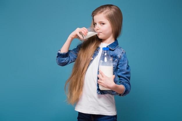 Menina bonita na jaqueta jeans com longos cabelos castanhos segurar o recipiente de leite