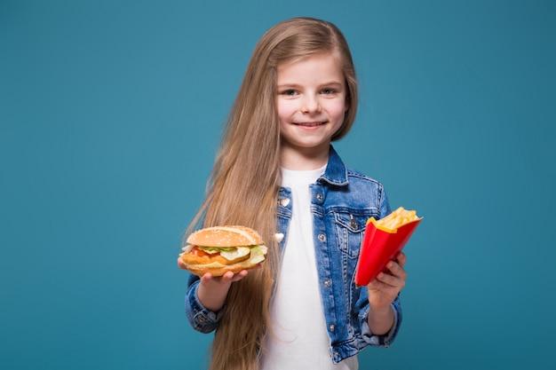 Menina bonita na jaqueta jeans com longos cabelos castanhos segurar um hambúrguer e batata frita