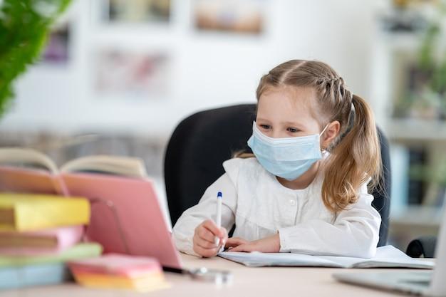 Menina bonita na máscara, fazendo lição de casa, e-learning