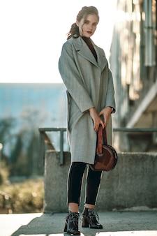 Menina bonita na moda com um casaco longo cinza