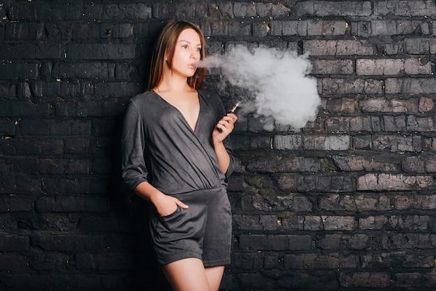 Menina bonita na moda fumando um cigarro sem tabaco, exalando grandes nuvens de fumaça. vestida com roupas da moda.
