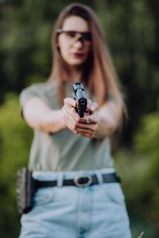 Menina bonita na natureza aprende a disparar uma pistola