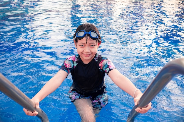 Menina bonita na piscina com sorriso e feliz no verão