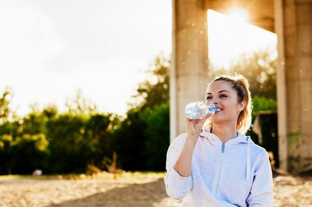 Menina bonita na roupa do esporte que bebe a água após o exercício na praia