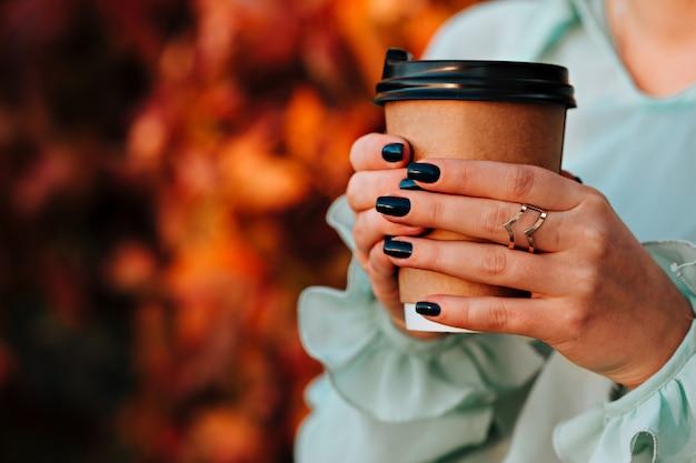 Menina bonita na rua outono segura um copo com uma bebida quente nas mãos