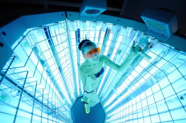 Menina bonita na superfície do dispositivo para o tratamento da luz. fototerapia