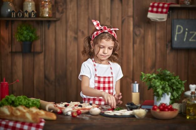 Menina bonita no avental xadrez, cozinhar pizza