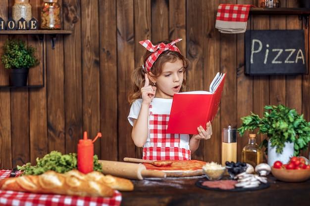 Menina bonita no avental xadrez, lendo o livro de receitas