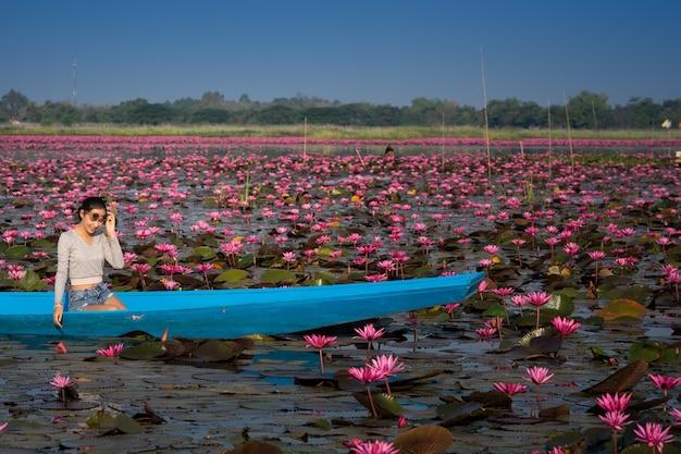 Menina bonita no barco azul no lago cor-de-rosa dos lótus na manhã. proteção solar.