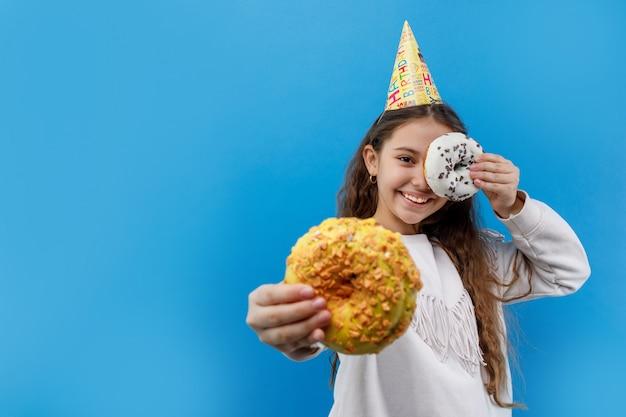 Menina bonita no boné de aniversário segurando duas rosquinhas e posando em azul