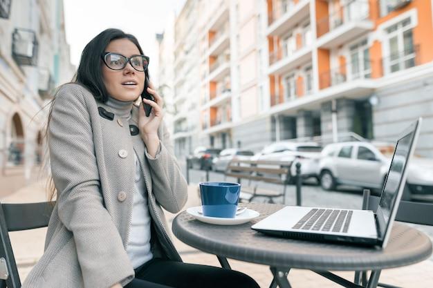 Menina bonita no café ao ar livre com laptop