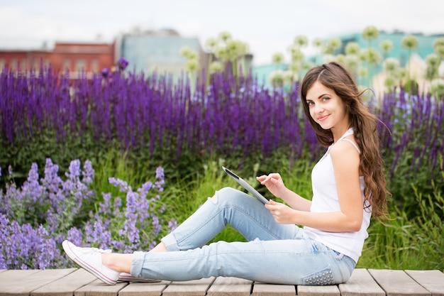 Menina bonita no campo de lavanda usando tablet
