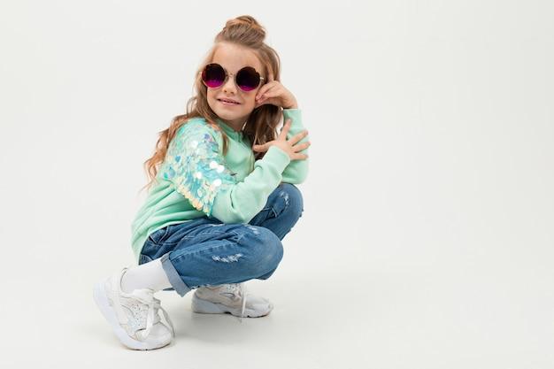 Menina bonita no capuz azul e óculos de sol senta-se e sorrisos isolados no branco