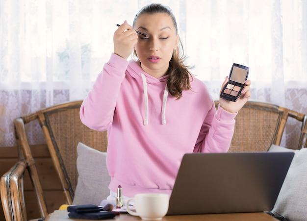 Menina bonita no capuz rosa fazendo maquiagem mostrando sombra para a câmera do laptop