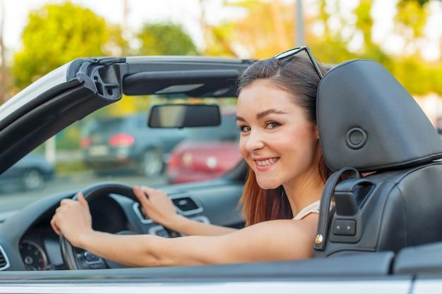Menina bonita no carro cabrio conversível em um dia ensolarado em uma cidade