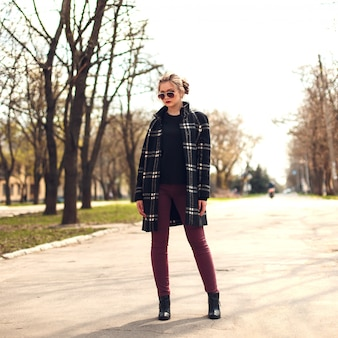 Menina bonita no casaco xadrez e óculos de sol em pé em um strreet