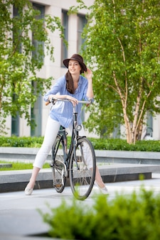 Menina bonita no chapéu andando de bicicleta na rua