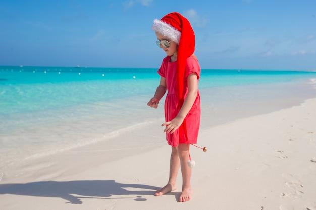 Menina bonita no chapéu de papai noel vermelho na praia