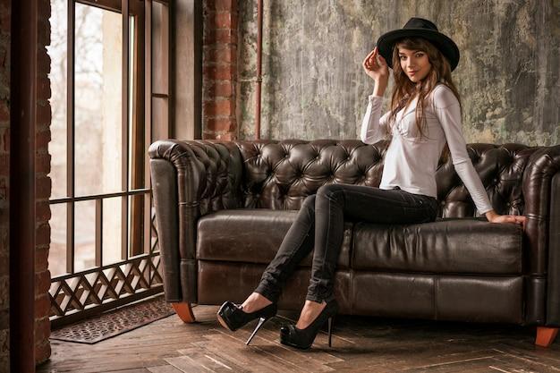 Menina bonita no chapéu preto sentado no sofá, mulher elegante