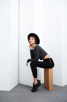 Menina bonita no chapéu, sentado na caixa sobre parede branca