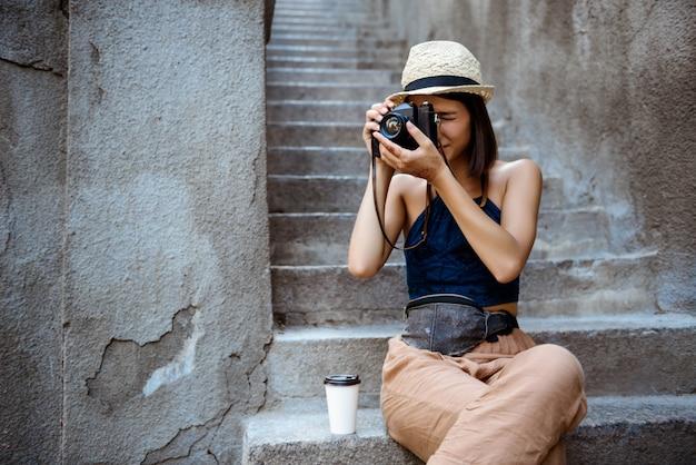 Menina bonita no chapéu, sorrindo, tirando fotos, sentado na escada.