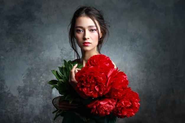 Menina bonita no concurso vestido verde com peônias de flores buquê nas mãos. modelo brincalhão, olhando para a câmera