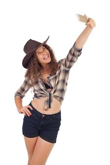 Menina bonita no estilo cowboy, fazendo selfie em seu smartphone.