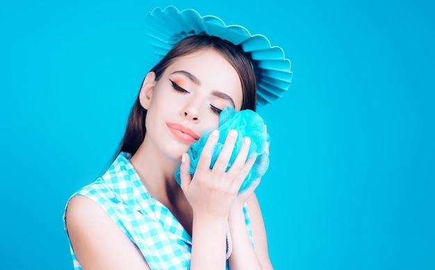 Menina bonita no estilo vintage, lavando-se com uma esponja.