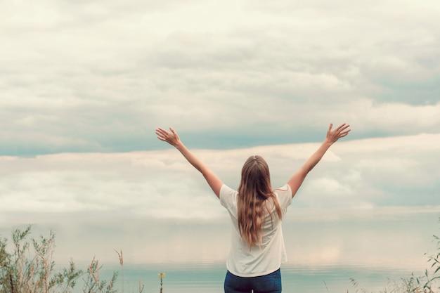 Menina bonita no lago. a vista de trás. mãos ao ar. céu nublado, pôr do sol