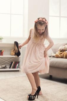 Menina bonita no lugar da mãe. pequena fashionista experimentando salto alto em casa, copie espaço