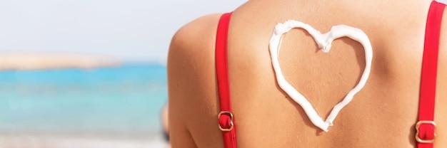 Menina bonita no maiô vermelho tem protetor solar em forma de coração na parte de trás na praia