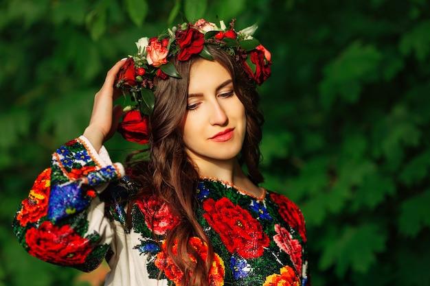 Menina bonita no pano tradicional ucraniano colorido com coroa de flores