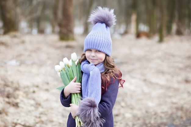 Menina bonita no parque com um buquê de tulipas brancas. buquê de tulipas. flores como um presente para o dia das mães das mulheres. 8 de março. o conceito de primavera e o dia da mulher. páscoa. closeup retrato c