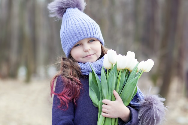 Menina bonita no parque com um buquê de tulipas brancas. buquê de tulipas. flores como um presente para o dia das mães das mulheres. 8 de março. o conceito de primavera e o dia da mulher. páscoa. closeup retrato criança