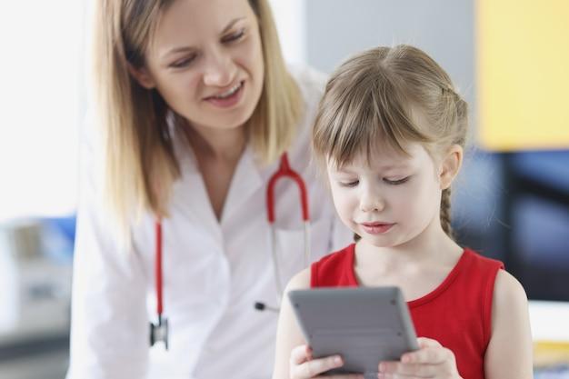 Menina bonita no pediatra está segurando o custo da calculadora do exame de crianças e