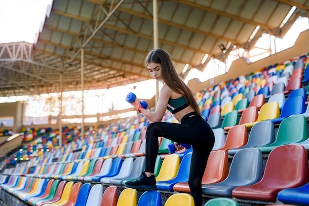 Menina bonita no sportswear malhando com halteres no estádio da cidade no verão. conceito de esportes