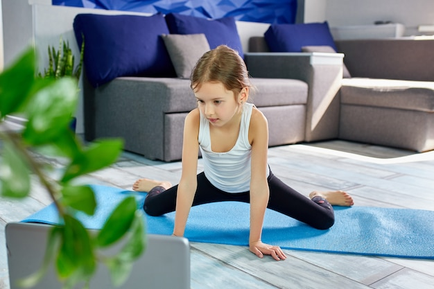 Menina bonita no sportswear no tapete azul praticando ginástica em casa