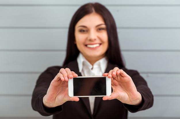 Menina bonita no terno clássico que mostra o telefone móvel.