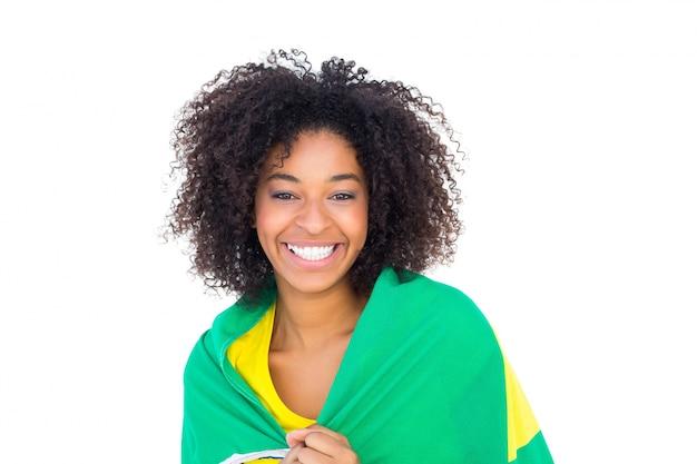 Menina bonita no tshirt amarelo que guardara a bandeira brasileira que sorri na câmera