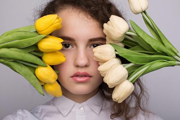 Menina bonita no vestido com tulipas flores nas mãos