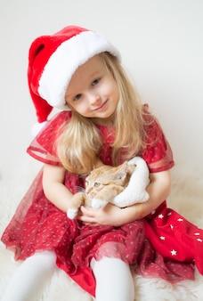 Menina bonita no vestido de festa vermelho de chapéu de papai noel com gatinho de gengibre esperando o natal