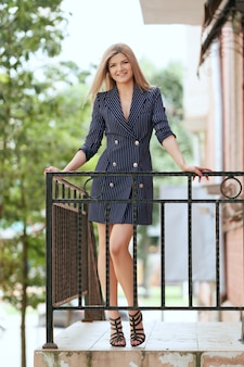 Menina bonita no vestido de jaqueta na varanda