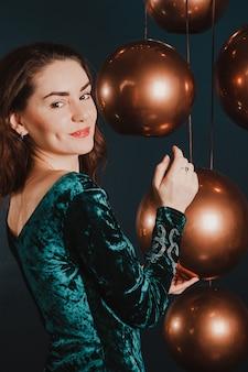 Menina bonita no vestido de luxo, brincando com bolas de ouro, ano novo ou conceito de natal