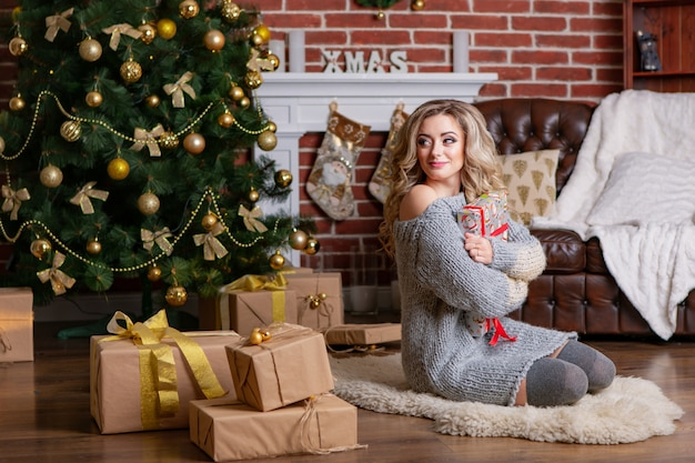 Menina bonita no vestido de malha é senta-se no chão e posa com um presente em suas mãos no fundo de um interior de natal