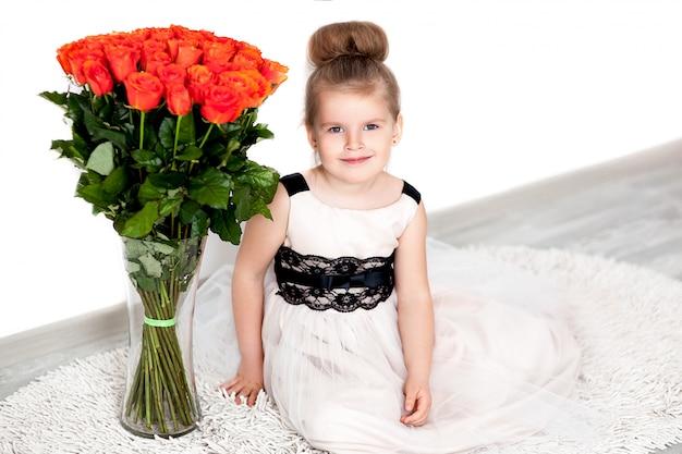 Menina bonita no vestido elegante com um buquê de rosas laranja