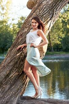 Menina bonita no vestido elegante no parque