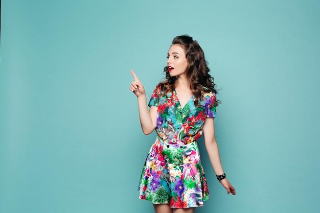 Menina bonita no vestido floral, apontando com o dedo.